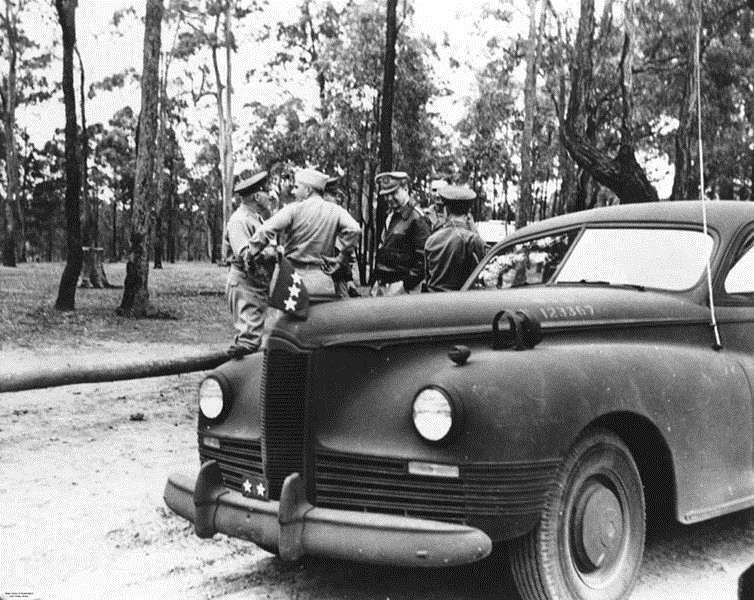 General Douglas MacArthur standing with five other soldiers at Camp Strathpine, 1944