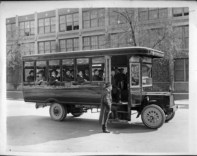 Packard bus in front of plant