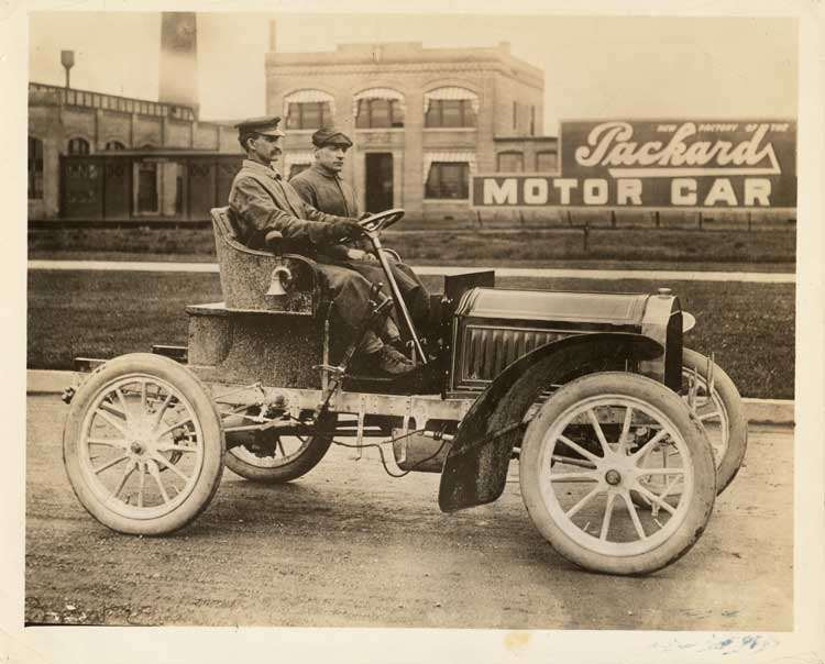 1904 Packard Model L with driver & passenger in front of Packard Motor Car Co.