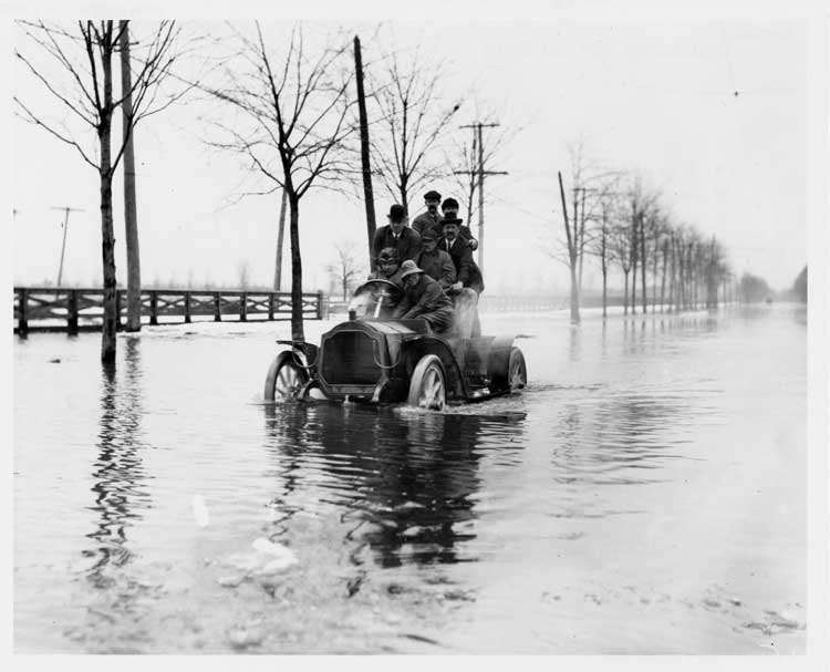 1905 Packard on water-covered road with seven men aboard