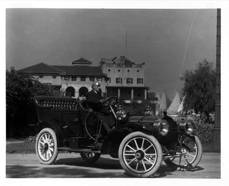 1909 Packard 30 Model UB touring car with male driver in front of the Detroit Boat Club