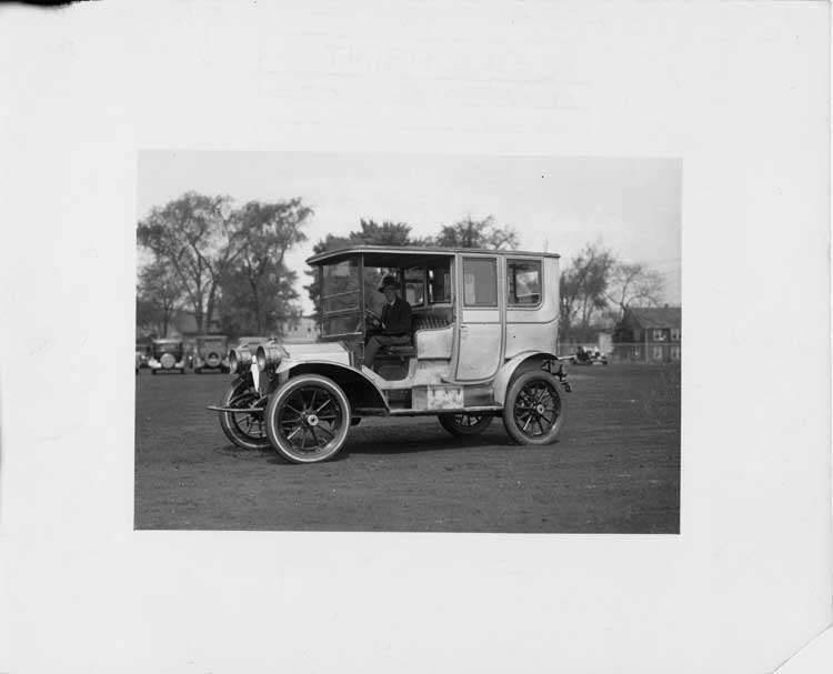 1909 Packard 30 Model UB limousine on lawn with male chauffeur