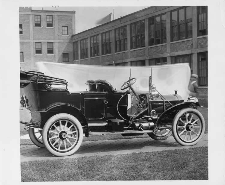 1909 Packard 30 Model UB touring car, right side, brick factory buildings in background