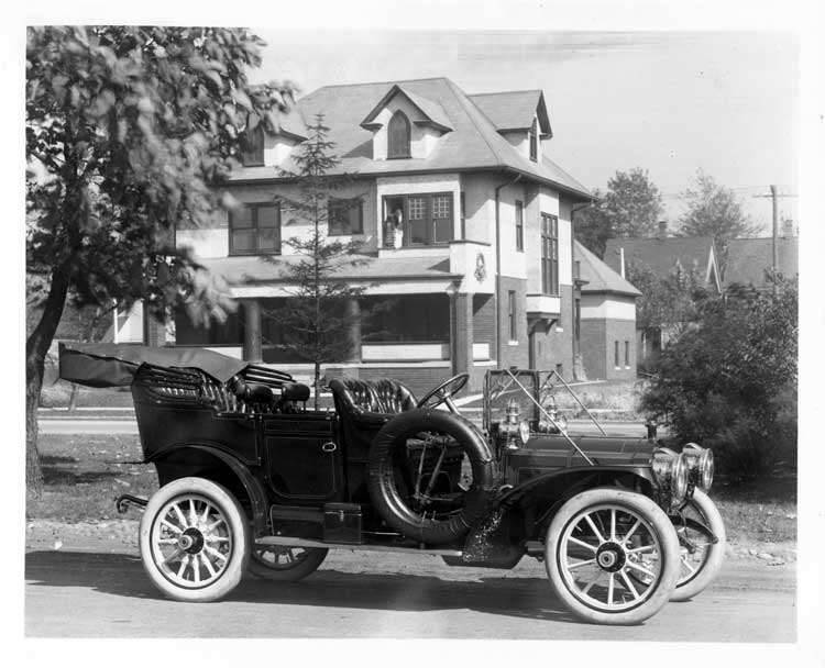 1909 Packard 30 Model UB touring car, parked on street in front of large house