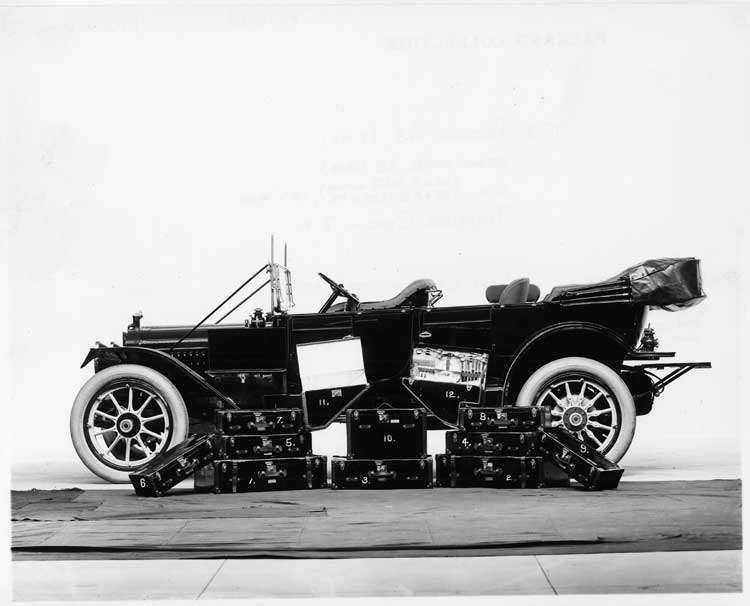 1913 Packard 48 touring car, left side, top folded with traveling cases piled alongside