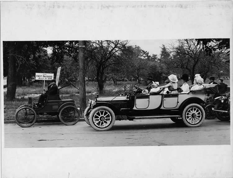 1899 Packard Model A roadster with 1913 Packard 48 touring car, on street with passengers