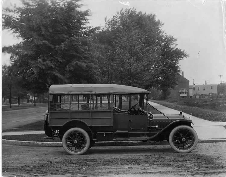 1913 Packard 38 station wagon, left side, parked on street, house in background