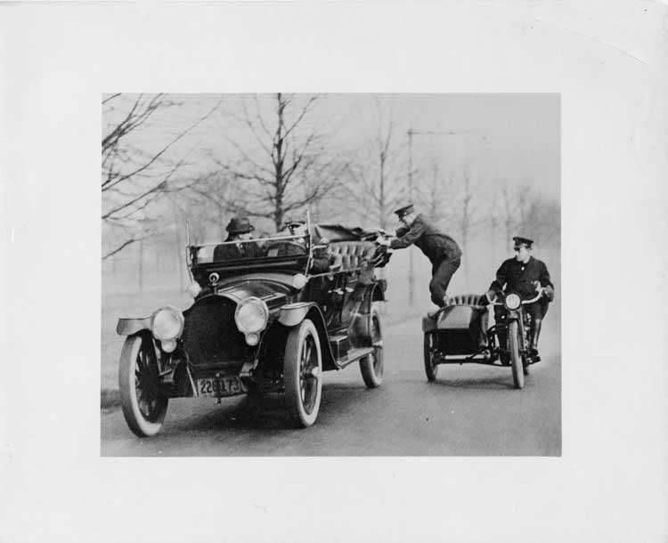 1916 Packard 1-25 phaeton, driving alongside a motorcycle and sidecar with two policemen