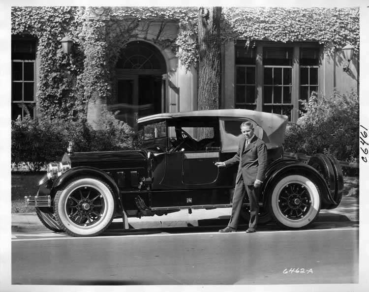 1916 Packard cloverleaf roadster parked on street in front of large, ivy-covered building