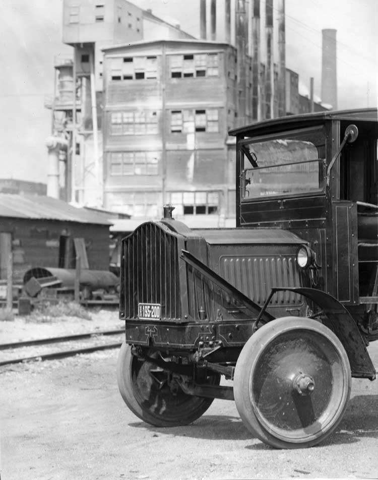 1918-1919 Packard truck, close-up view of the front quarter, factory in background