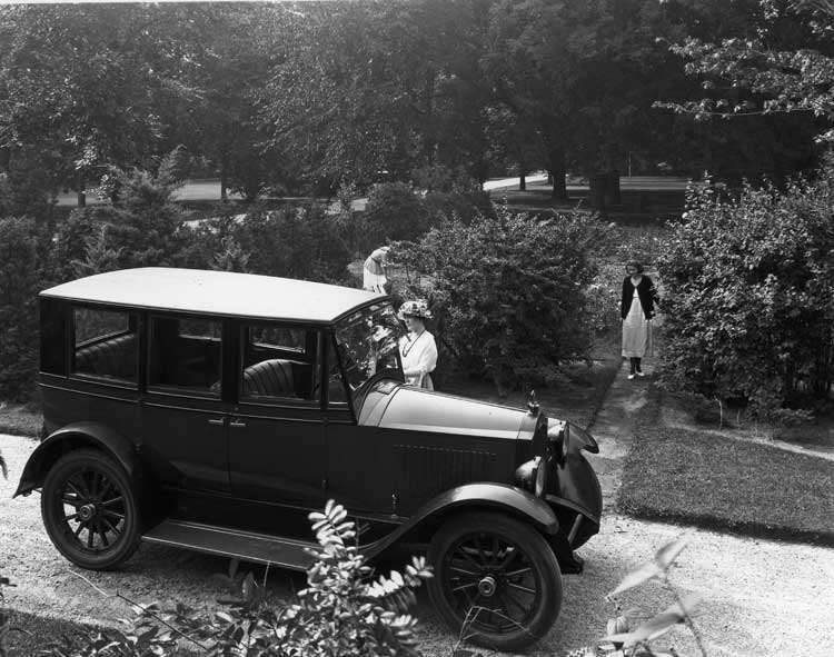 1921-1922 Packard sedan parked in drive next to garden