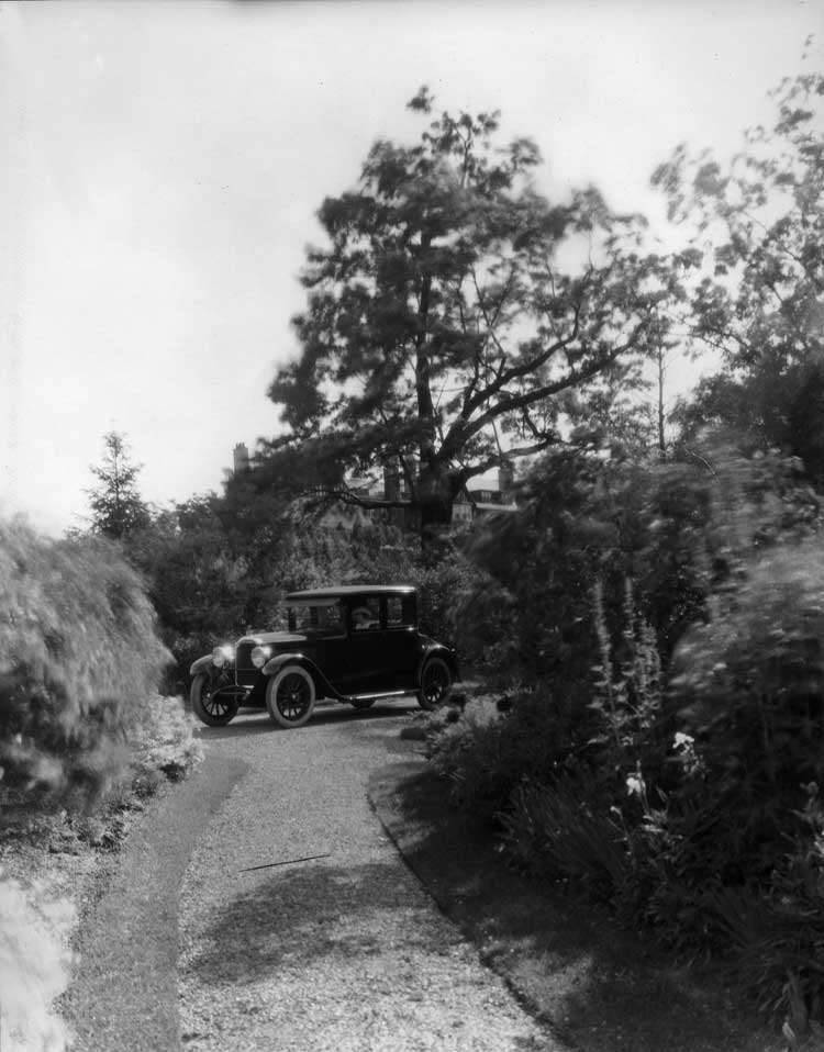 1922 Packard coupe with a female driver, rounding corner
