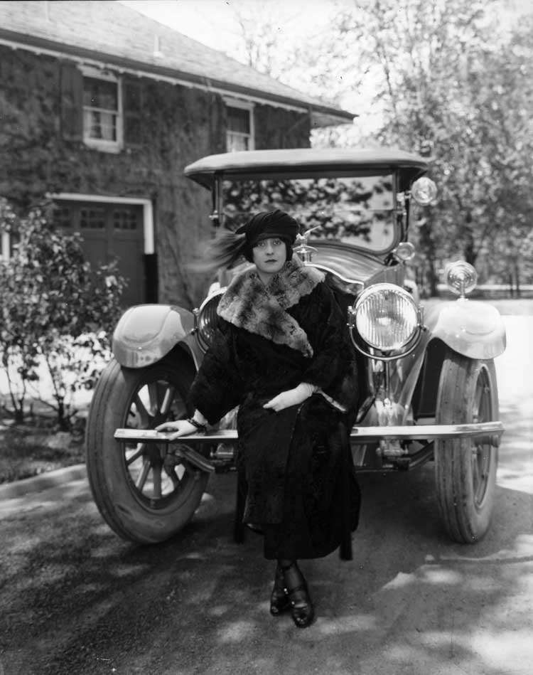 1922 Packard touring car, front view with female standing in front, parked on drive, garage in backg