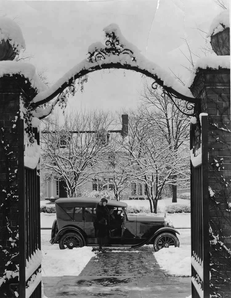 1922 Packard touring car, parked on street, seen through large iron gate in winter