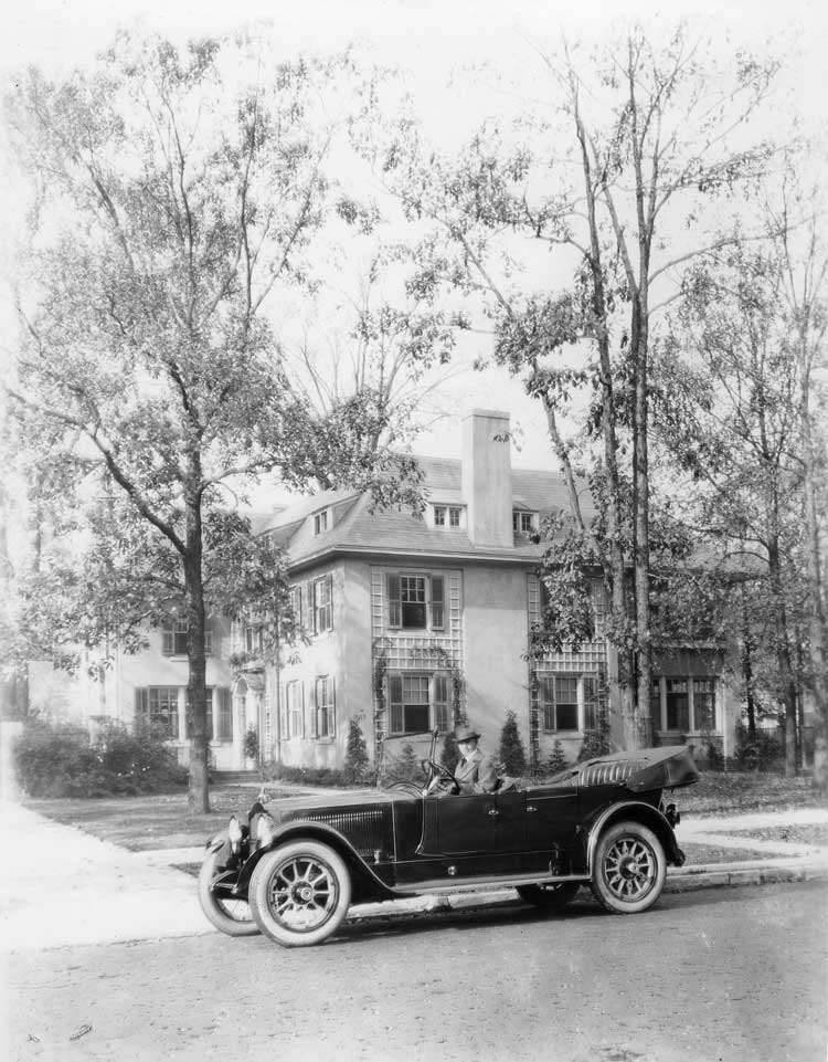 1920-1923 Packard touring car in front of large home, Alvan Macauley in driver's seat
