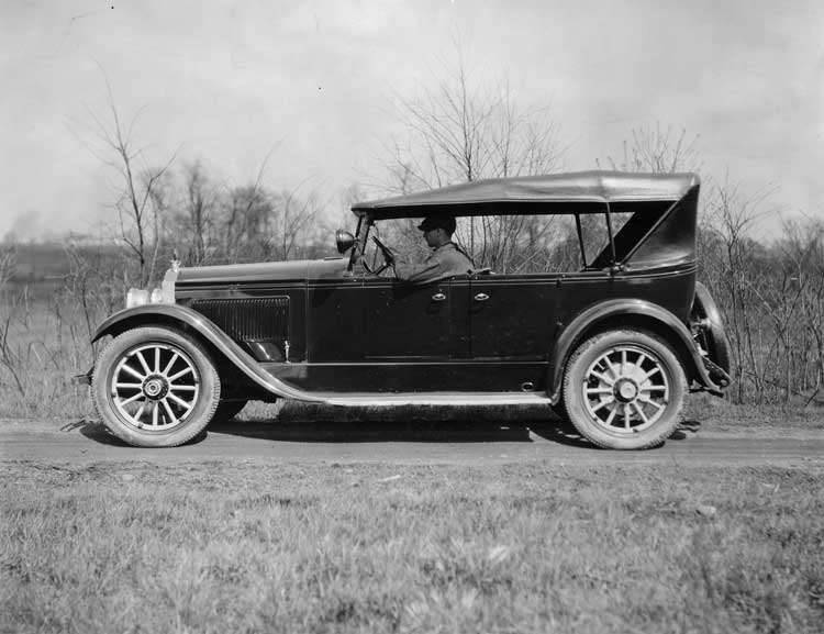 1922-1923 Packard touring car, left side view, top raised, male driver, on country road