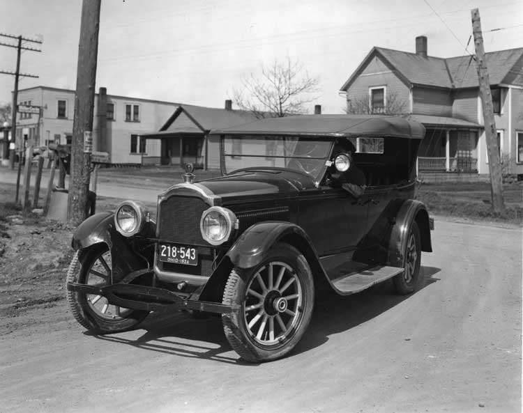 1923 Packard touring car coming around corner on residential street