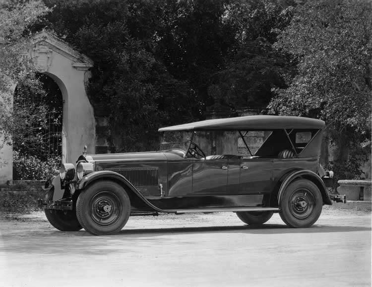 1923 Packard touring car parked by stone arch