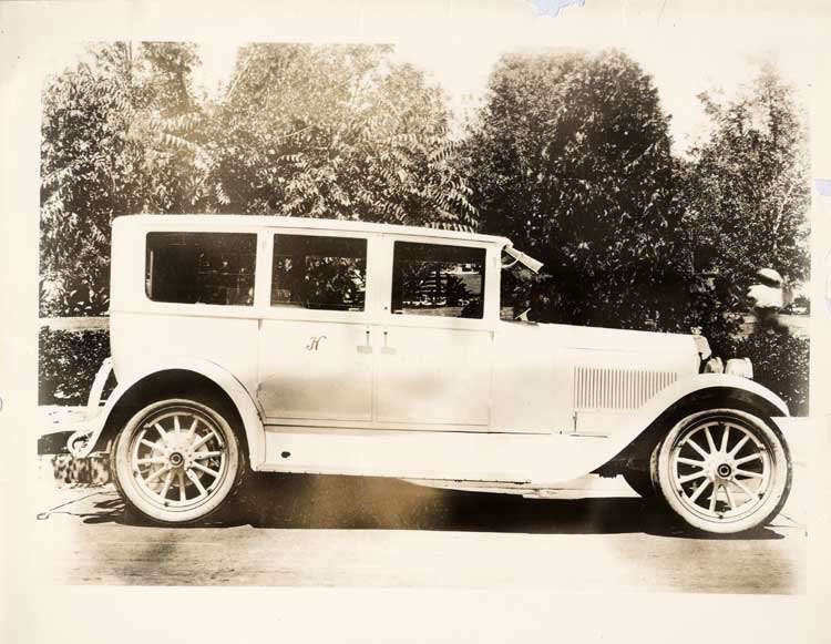 1924 Packard sedan, right side view, parked on street, 'H' on monogram panel