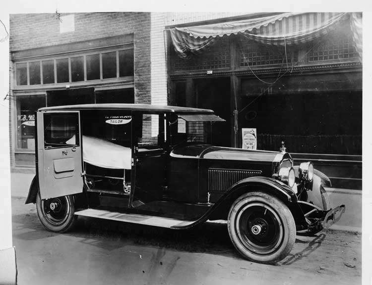 1924 Packard ambulance, doors open, parked on street