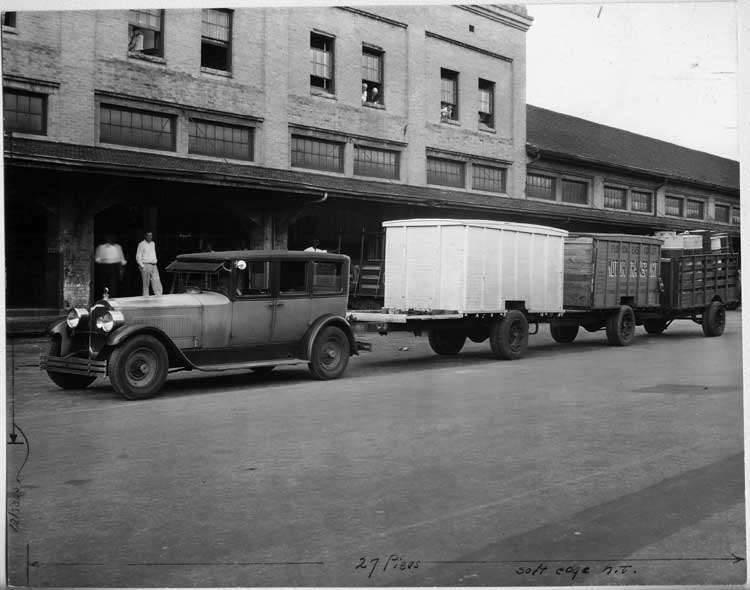 1924 Packard sedan, three-quarter left front view, hauling three cargo wagons