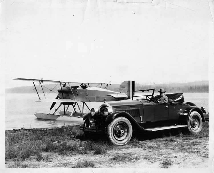 1924 Packard runabout parked next to lake with plane