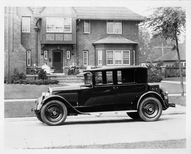 1925 Packard left side view, parked on residential street, in front of large brick home