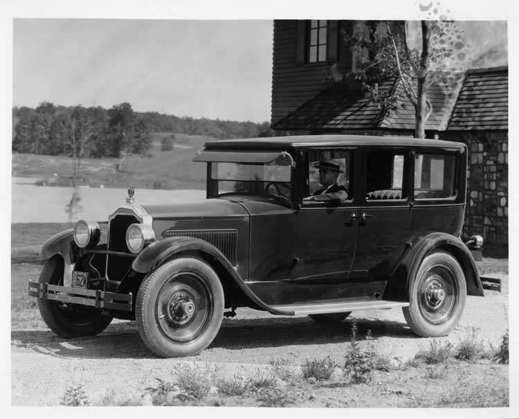 1925 Packard sedan, three-quarter left front view, male driver, parked in front of large home