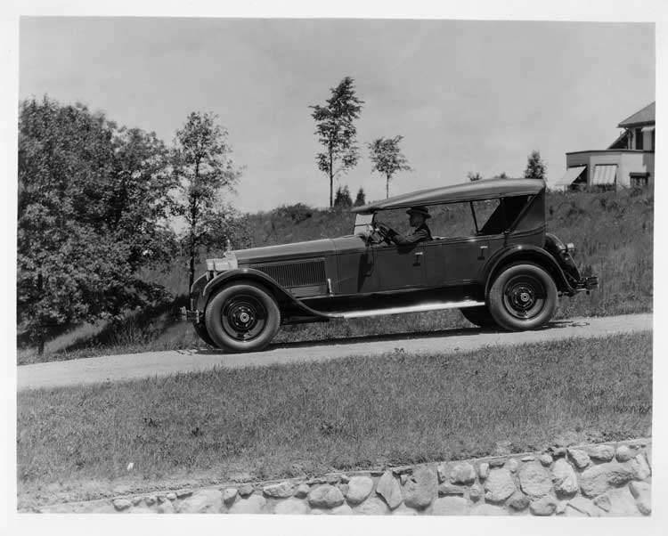 1925 Packard touring car, left side view, top raised, with male driver on country road