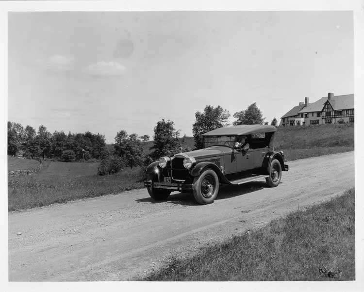 1925 Packard touring car, three-quarter left front view, top raised, with male driver on country roa