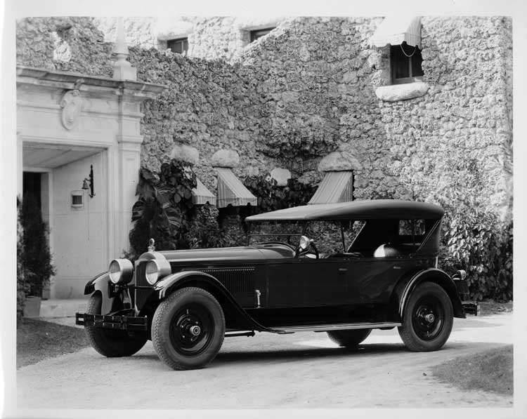 1925 Packard touring car, seven-eights left front view, parked in front of large home, top raised
