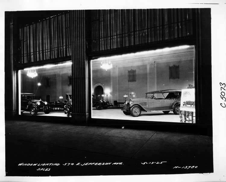1925 Packards in dealership showroom, through window at night