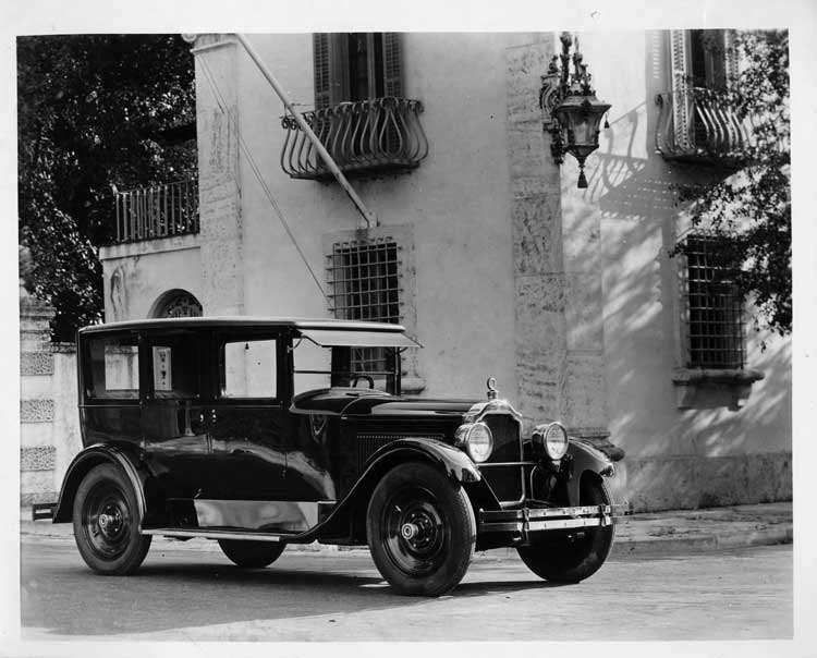 1925 Packard sedan, three-quarter right front view, parked in front of large home