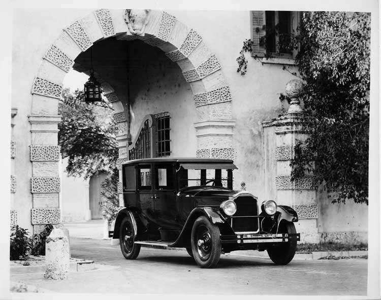 1925 Packard sedan parked under stone archway of large house