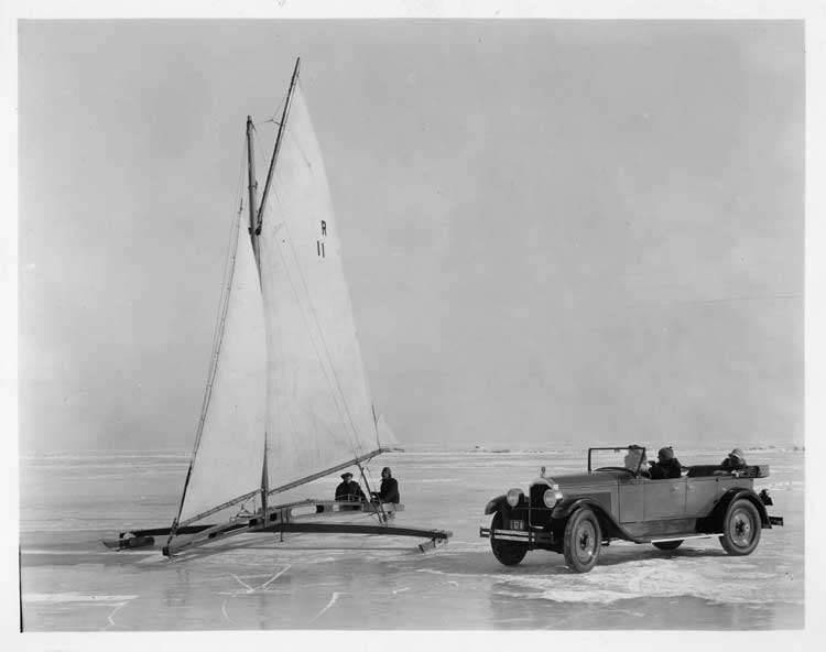 1925 Packard touring car parked on frozen lake next to an ice boat