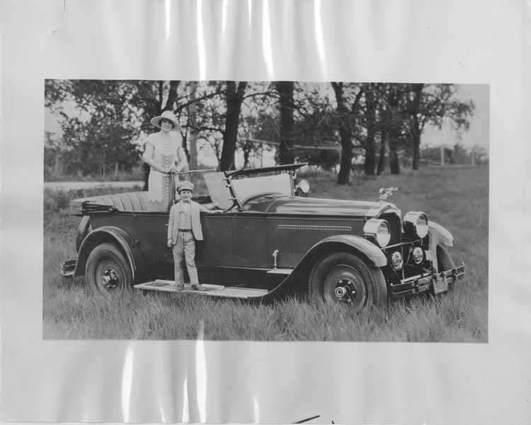 1925 Packard Model 236 sport parked in field, small boy standing on running board