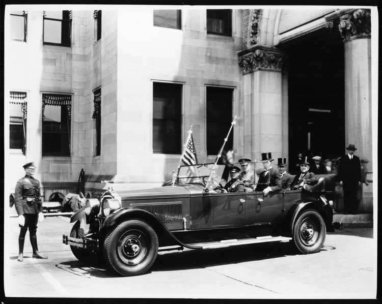 1925-1926 Packard touring car with American flag parked in front of large stone building