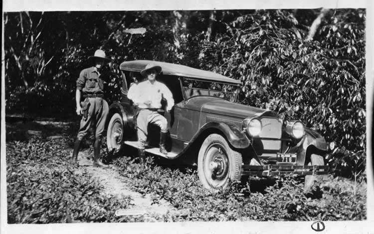 1925-1926 Packard sport model, front view, top raised, two men standing at side, on jungle road