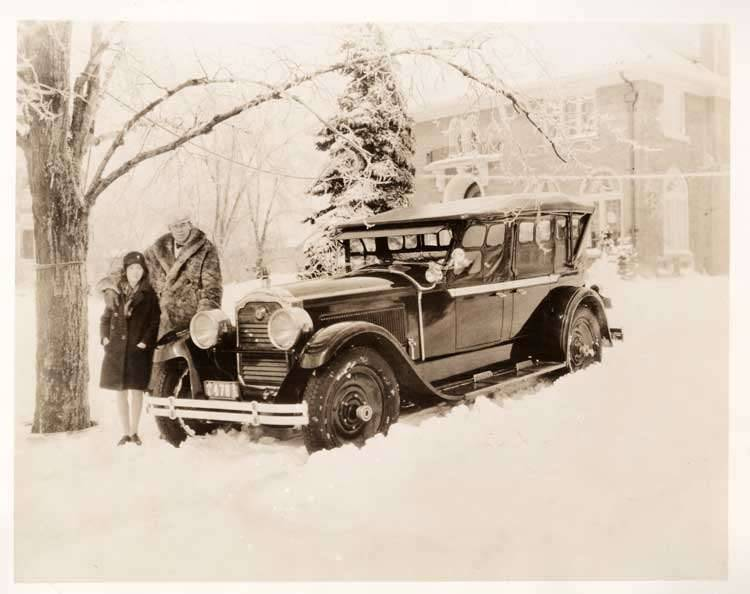 1925-1926 Packard touring car on snowy day, with couple