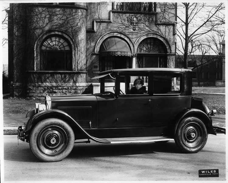 1925-1926 Packard coupe, parked on street in front of house, female driver