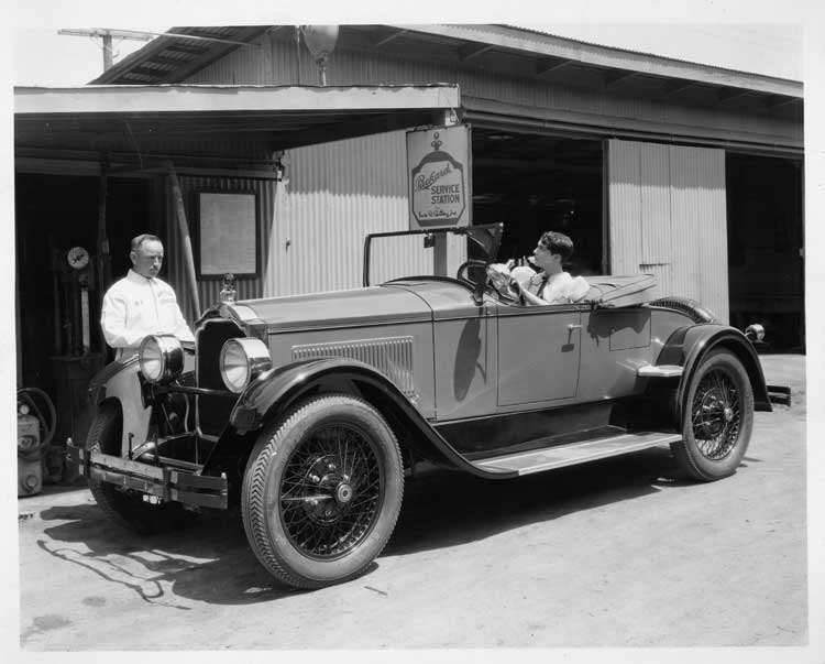 1925-1926 Packard runabout, actress Leatrice Joy behind wheel in front of a Packard service station