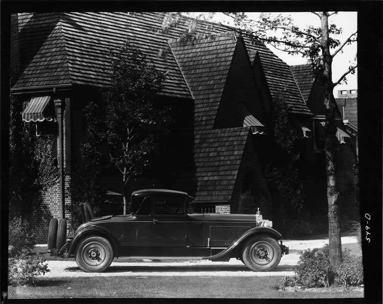 1928 Packard stationary coupe, right side view, parked in drive way, house in background