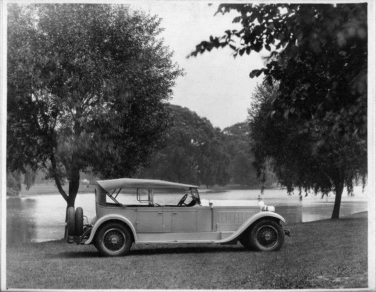 1928 Packard phaeton, nine-tenths right rear view, top raised, water and trees in background
