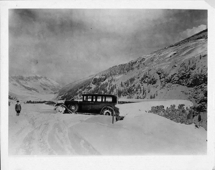 1928 Packard sedan on a snowy road with Swiss Alps in background