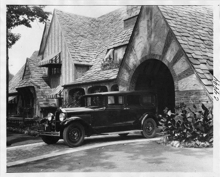 1930 Packard sedan limousine, three-quarter left side view, parked on drive at side of large brick h