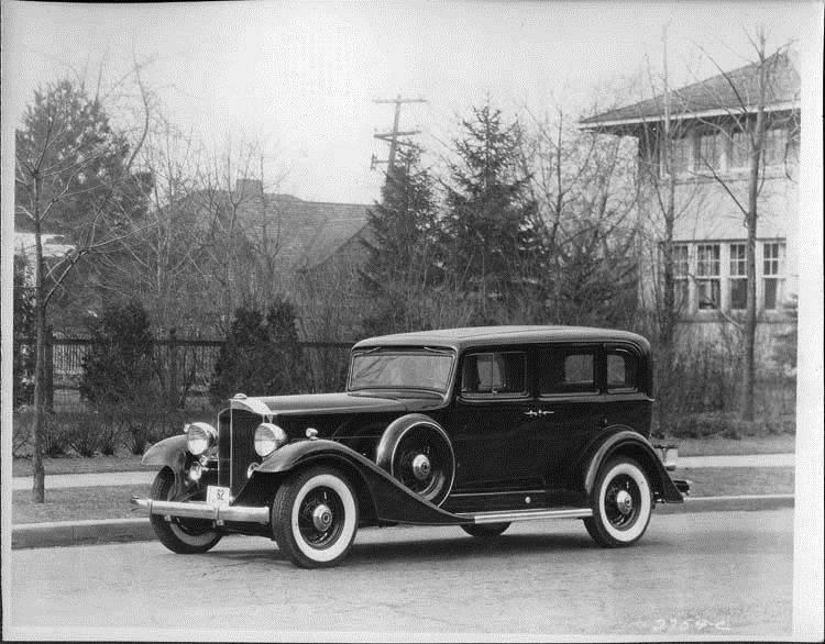 1933 Packard sedan, three-quarter left side view, parked on street
