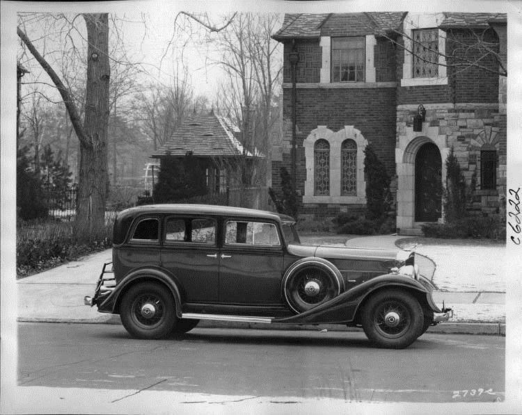 1933 Packard sedan, right side view, parked on street in front of house