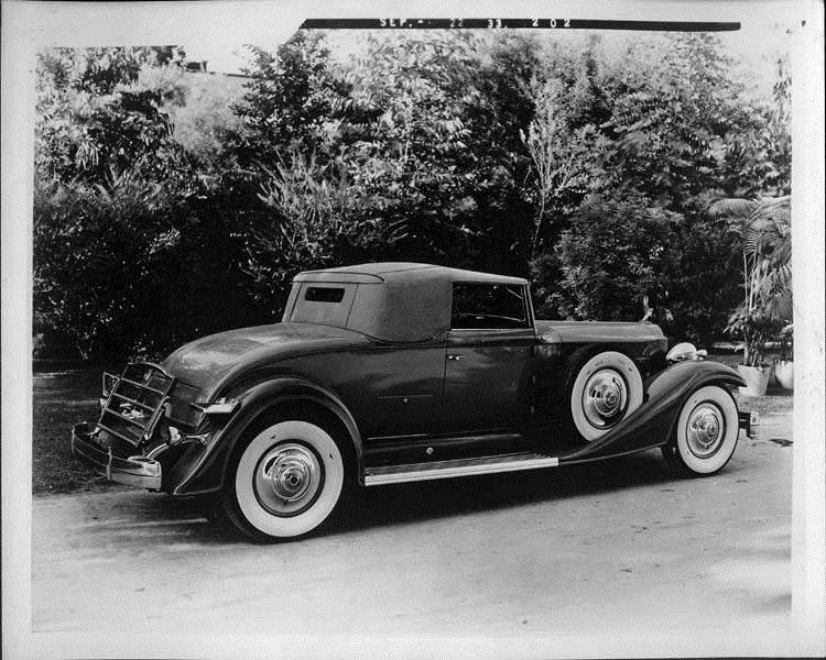 1933 Packard coupe-roadster, three-quarter rear right view, top raised, parked on drive