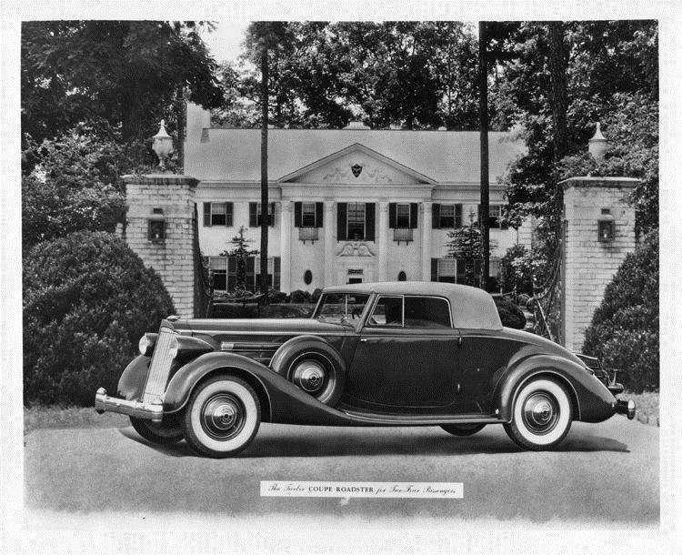 1936 Packard coupe roadster, parked in front of gateway, house in background
