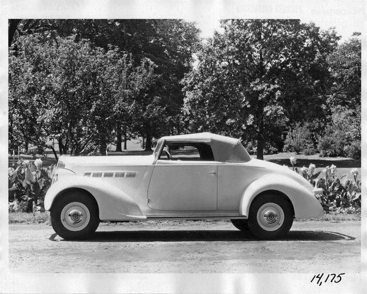 1936 Packard convertible coupe, top raised, parked on scenic dirt road